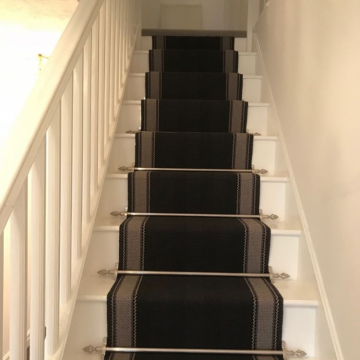 Roger Oates, Henley Soft Black to the stairs with Dubai stairrods and Simply Natural Ribgrass Breccia to the landing supplied and installed by Arighi Bianchi